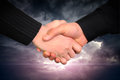 Handshake concept on dramatic cloudscape area with ray of light Royalty Free Stock Photography
