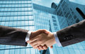 Handshake of two businessmen on the background business buildings Royalty Free Stock Photos