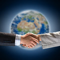 Handshake of two businessmen on the background the planet earth elements this image are furnished by nasa Stock Photo
