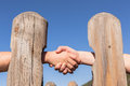 Handshake wood distant trust through poles in abstract blue Royalty Free Stock Photos