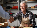 Handshaking at workshop smiling senior carpenter greeting customer and shaking his hand small business Stock Photo