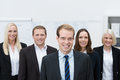 Handsom young manager with a happy team behind him caucasian smiling made of three women and man Stock Photography