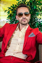 Handsome adult model wearing red jacket and fashionable sunglasses tree on the background Stock Image