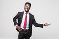 Handsome African American man in a black business suit gesturing as if to demonstrate a product sample on grey Royalty Free Stock Photo