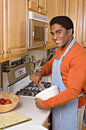 Handsome African-American man cooks in kitchen Stock Images