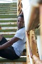 Handsome african american man sitting on stairs outdoors portrait of a Royalty Free Stock Image