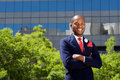Handsome african businessman smiling by building in city