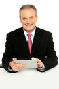 Handsome aged business male using tablet pc Stock Images