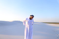 Handsome Arab sheik suffers from discomfort in back, standing in