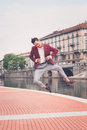 Handsome asian model jumping by an artificial basin young dressed in red blazer Royalty Free Stock Photography