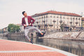 Handsome asian model jumping by an artificial basin young dressed in red blazer Stock Photography
