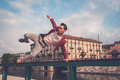 Handsome asian model jumping in the city streets young dressed red blazer a balustrade Stock Photography