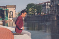 Handsome asian model sitting by an artificial basin young dressed in red blazer Royalty Free Stock Images