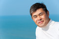 Handsome asian young man looks into camera smiling blue sea and sky Stock Images