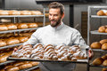 Handsome baker holding tray full of freshly baked croisants in uniform croissants at the manufacturing Royalty Free Stock Image