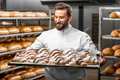 Handsome baker holding tray full of freshly baked croisants in uniform croissants at the manufacturing Royalty Free Stock Photo