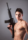 Handsome bare chested soldier is holding a rifle on black background Royalty Free Stock Photo