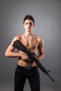 Handsome bare chested soldier is holding a rifle on black background Royalty Free Stock Photos