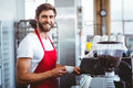 Handsome barista using the coffee machine