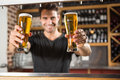 Handsome barman holding a pint of beer in pub Stock Photos