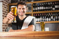 Handsome barman holding a pint of beer Royalty Free Stock Photo