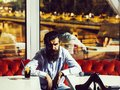Bearded man between two tables Royalty Free Stock Photo
