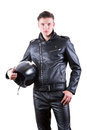 handsome biker man wearing black leather jacket and pants holding motorcycle helmet Royalty Free Stock Photo