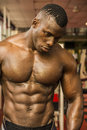 Handsome black male bodybuilder resting after workout in gym Royalty Free Stock Photo
