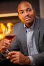 Handsome black man with cigar and a glass of wine sitting by fireplace smoking drinking Stock Photo