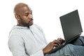 Handsome black man typing on a laptop late s the computer isolated white background Stock Photo