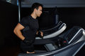 Handsome brunette man doing workout in gym running on treadmill Royalty Free Stock Photo