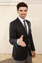 Handsome business man smiling inviting to a handshake portrait of young focus on the hand Stock Photo