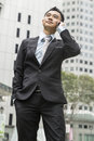 Handsome business man speaking mobile phone at his company office building model is a asian male Stock Photos