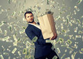 Handsome businessman holding money successful heavy paper bag with under dollar s rain Royalty Free Stock Image