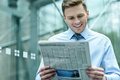 Handsome businessman reading a newspaper business executive and smiling Royalty Free Stock Images