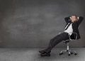 Handsome businessman resting in his swivel chair a grey empty room Stock Images