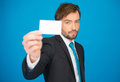 Handsome businessman showing blank business card on blue Royalty Free Stock Images