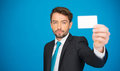 Handsome businessman showing blank business card on blue Royalty Free Stock Photography