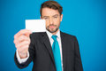 Handsome businessman showing blank business card on blue Royalty Free Stock Photo