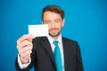Handsome businessman showing blank business card on blue Stock Photos