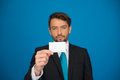 Handsome businessman showing blank business card on blue Royalty Free Stock Photos