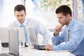 Handsome businessmen busy by working young on laptop in bright office Royalty Free Stock Photo