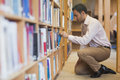 Handsome casual man cowering in front of bookshelves taking a book off a shelf Stock Photography