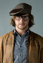 Handsome caucasian man portrait of a wearing a leather jacket blue checkered button shirt beret and retro glasses Stock Images