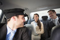 Handsome chauffeur smiling at clients in the car Stock Photo