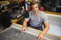 Handsome cheerful radio host moderating sitting in studio at college Stock Photos