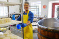 Handsome cheesemaker making curd cheese in his factory Royalty Free Stock Photo