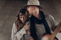 Handsome cowboy man with a guitar kissing beautiful indie woman Royalty Free Stock Photo