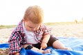 Handsome curious child sitting on sand on the beach playing Royalty Free Stock Photo