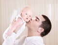 Handsome daddy kissing daughter cute little toddler men enjoying time spend with his little newborn at home love concept Stock Image